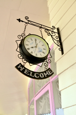 Vintage style clock hanging  With signs welcoming  photo