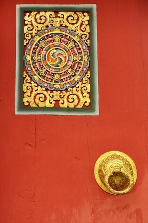 Orange-red door with gold handles and designs of Bhutanese  photo
