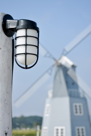 Lamp in the garden with a windmill in the background  photo
