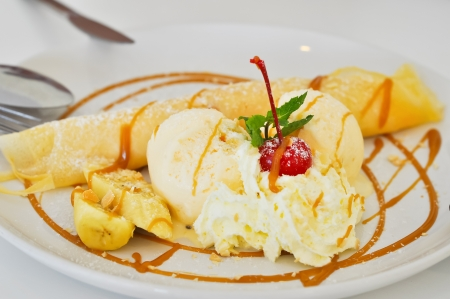 Vanilla ice cream and crepes stuffed with bananas topped with caramel and whipped cream. 免版税图像