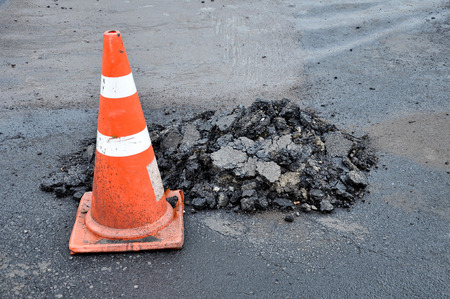 Traffic cones and mounds of asphalt, while road repairs.