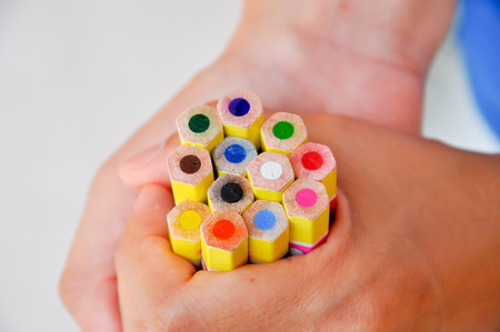 A brightly colored pencils in her handful. photo