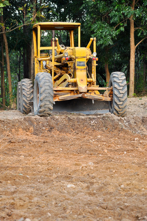 Graders are commonly used in the construction and maintenance of dirt roads and gravel roads. Stock Photo