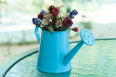 A little artificial flowers in a little watering can