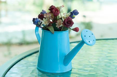 Een beetje kunstbloemen in een klein gieter