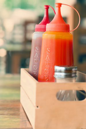 ketchup bottle: Ketchup and chilli sauce in small wooden box Stock Photo