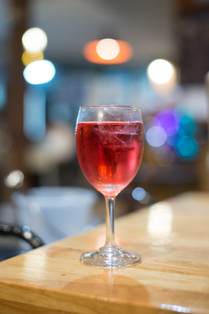 Wine in a glass on a bar under the bokeh light. Stock Photo