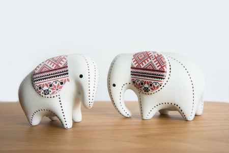 Small ceramic elephant on a wooden floor on a white background.