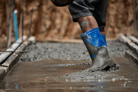 Workers are walking on concrete that is still liquid. Stock Photo