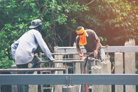 Workers are using Impact drill to drill concrete. Under sunlight
