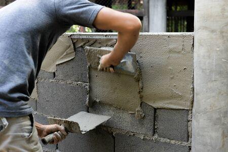 Asian plasterer plastering concrete walls