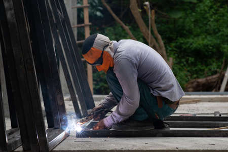 The laborer is welding steel in the construction.