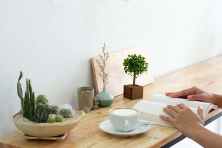 Mockup image of a woman reading a book on table with blank pages of book 免版税图像