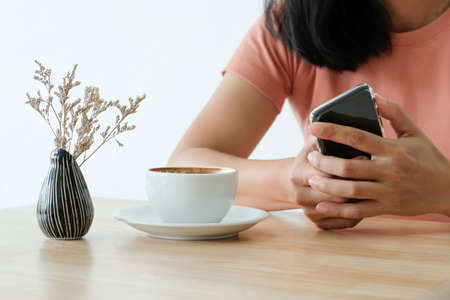 Woman holding smart phone during coffee time in the morning.