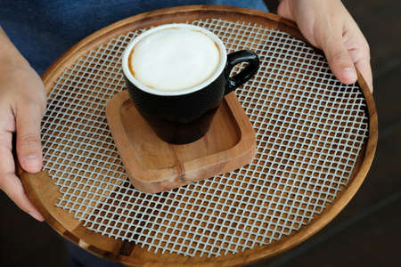 Professional waiter is serving cup of coffee on wooden tray 免版税图像