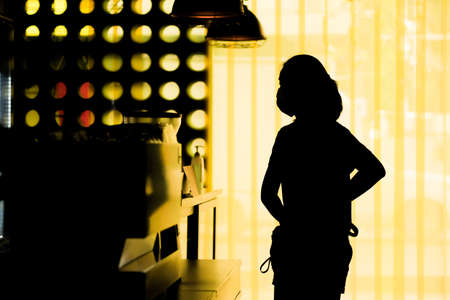 A silhouette of a woman wearing a mask while shopping for coffee in a coffee shop, spaced social distance from others during the coronavirus outbreak.