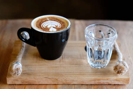 cappuccino coffee cups and warm water were served together on a wooden tray. 免版税图像