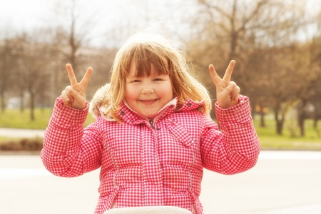 Happy little Girl is showing the victory hand sign photo