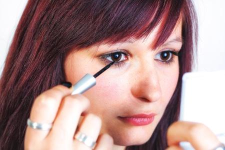 eyelid: Young beautiful woman applying eyeliner on eyelid - isolated on white background
