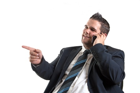 young businessman is pointing and talking over the cellphone, isolated on white background Stock Photo - 13653758