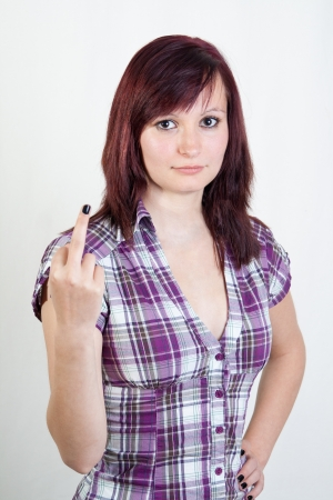 young redhead woman showing middlefinger isolated on white background photo