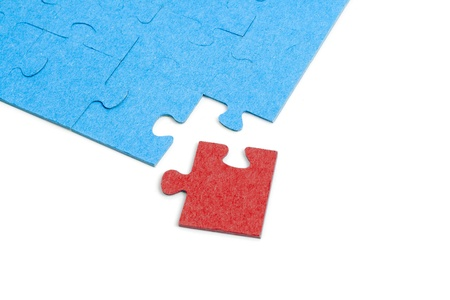 Blue Puzzle with one red jigsaw piece isolated on white background photo