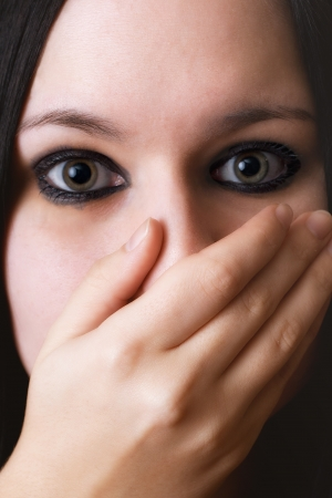 closeup black haired girl covering the face with her hand photo