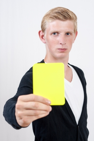 Attractive young man showing yellow card photo