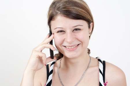 young smiling brunette girl is talking to someone over her smartphone  all on white background photo