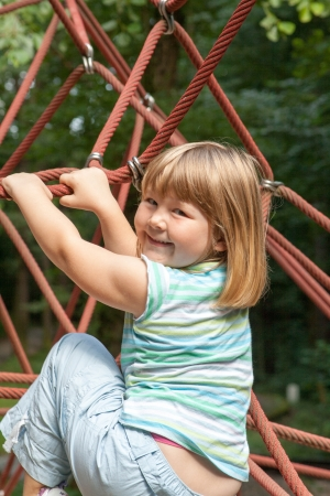 small blonde girl climbing a rope climbing frame photo