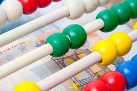 Education concept - Abacus with many colorful beads and banknotes in background photo