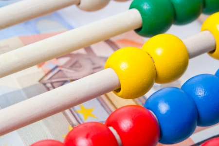 Education concept - Abacus with many colorful beads and banknotes in background Stock Photo - 15649610