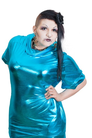 Dark-Haired woman with undercut hairstyle and piercings in her face wearing a blue shiny dress - all on white Background.