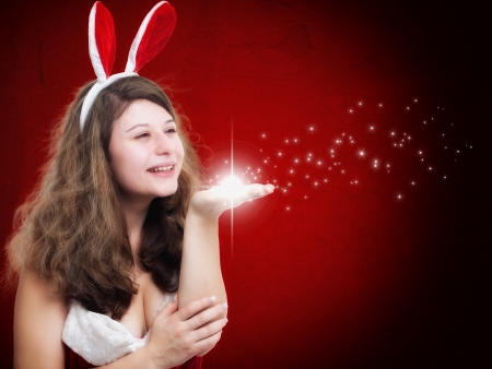 Christmas Woman blowing some stars on red background photo