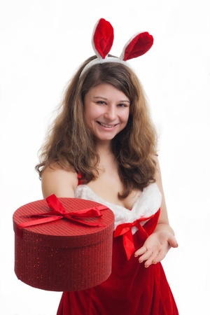 young christmas woman in red santa claus dress is giving a christmas present  Stock Photo - 16634670