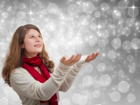 Winter woman holding hands up on grey background with stars and snowflakes photo