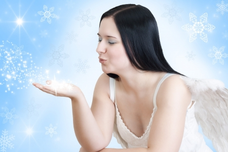 christmas angel with black hair and wings  blowing some stars on blue white background with stars and snow  photo