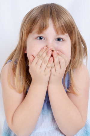 Portrait of a cute little girl covering her mouth with hands photo