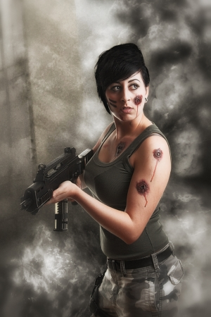 gunshot: wounded special tactics sexy woman holding up her weapon in a battlefield Stock Photo
