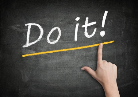 good attitude: Motivation text Do it! with a hand pointing to it on a blackboard Stock Photo