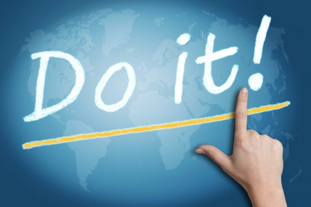 Motivation text Do it! with a hand pointing to it on blue background with a world map photo