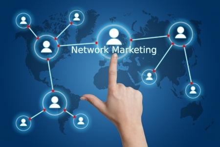 redes de mercadeo: concepto de negocio en Internet: la mano presionando un botón de mercadeo en red en una interfaz de mapa del mundo Foto de archivo