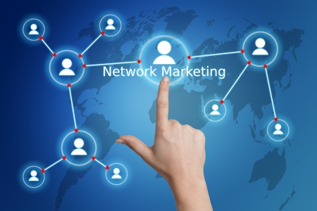 network marketing: internet business concept: hand pressing a network marketing button on a world map interface