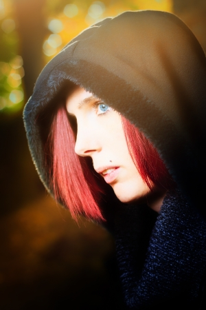 anorak: Head and shoulders portrait of a beautiful redhead woman with blue eyes standing in profile outdoors wearing a hooded anorak
