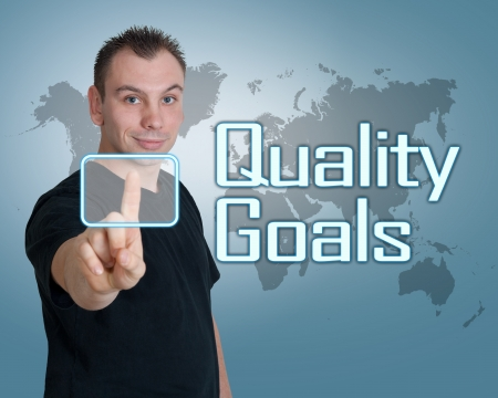 Young man press digital Quality Goals button on interface in front of him photo