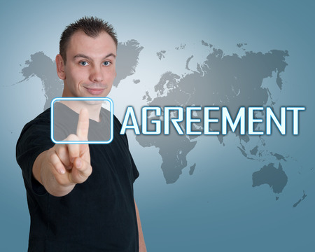 concur: Young man press digital Agreement button on interface in front of him Stock Photo
