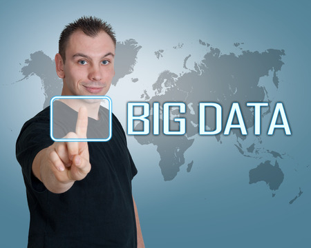 digital asset management: Young man press digital Big Data button on interface in front of him Stock Photo