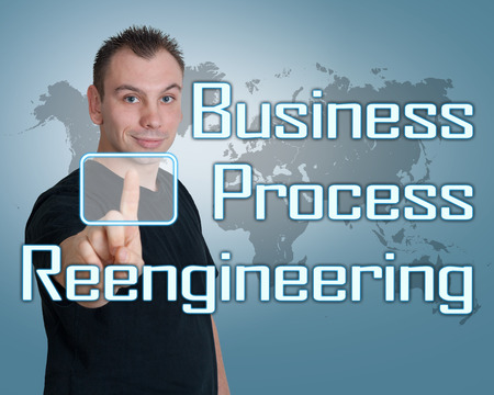 business process reengineering: Young man press digital Business Process Reengineering button on interface in front of him Stock Photo