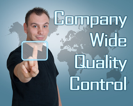 product design specification: Young man press digital Company Wide Quality Control button on interface in front of him Stock Photo