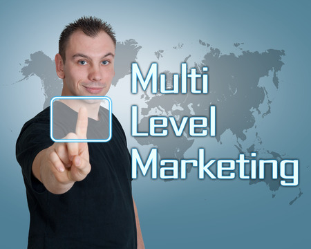 mlm: Young man press digital Multi Level Marketing button on interface in front of him Stock Photo